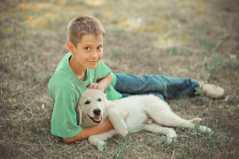 Retriever pup Lovely scene handsom teen boy enjoying summer time vacation with best friend dog ivory white labrador puppy.Happy ai. Rily careless childhood life royalty free stock photography