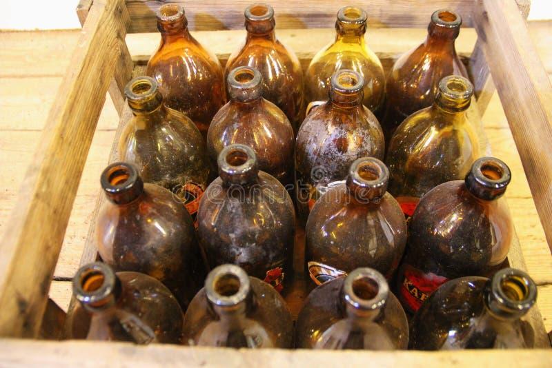 Retro ölflaskor i träask royaltyfri foto