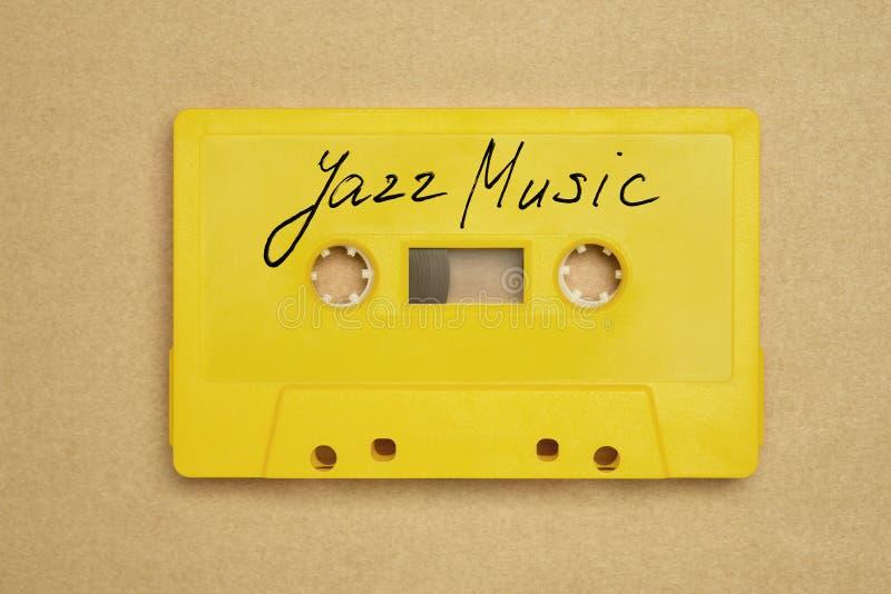 Retro żółta audio kasety taśma kłaść na papierowym tle z jazzową muzyką zdjęcia royalty free