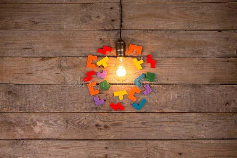 Retro żarówka i grupa wyrzynarki na drewnianym tle - pomysłu, innowacji, pracy zespołowej i przywódctwo pojęcie, Przestrze? dla t obraz royalty free