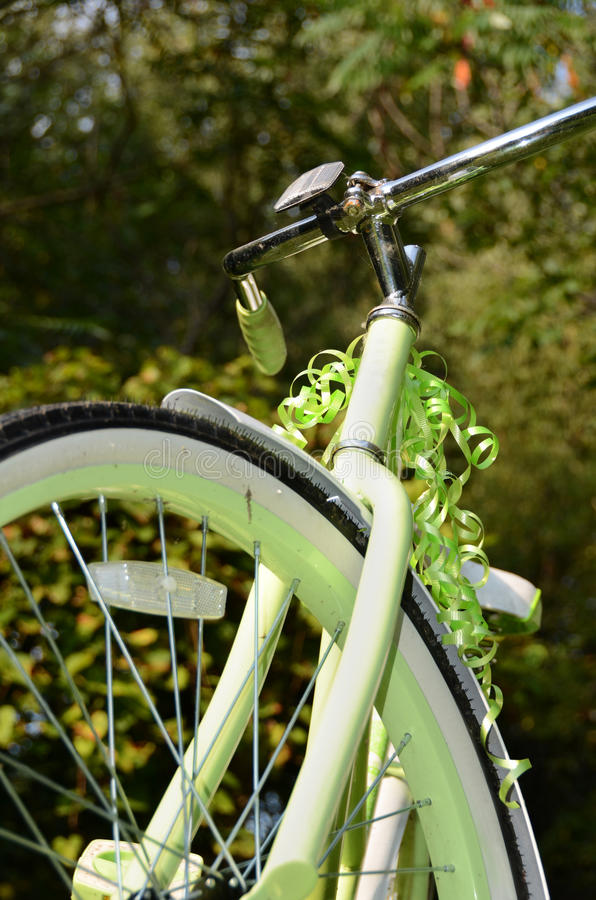 Retro adult bicycle ready to ride!. Retro adult bicycle, light green, silhouetted bike handlebars and front tire section against tree backdrop, copyspace. A gift royalty free stock photo