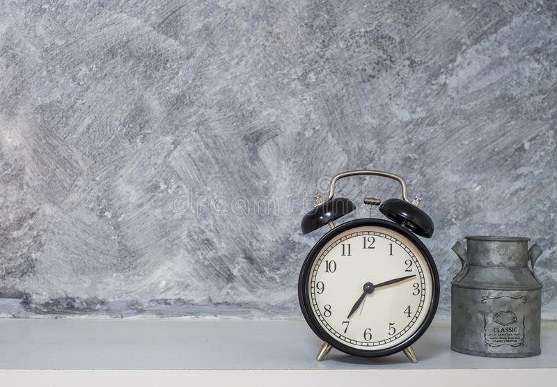 Retro alarm black clock vintage style with small milk bucket. Bare cement loft  wall background royalty free stock images