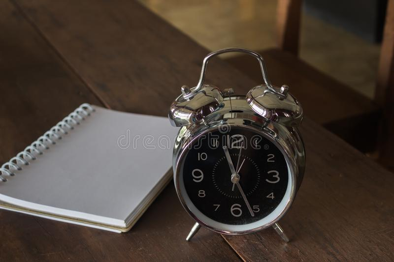 Retro alarm clock with blank realistic spiral notepad notebook o royalty free stock images