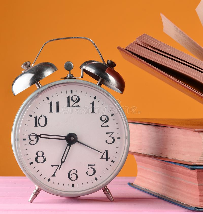 Retro alarm clock and books on a pink table on a yellow wall backgroun.d. Retro alarm clock and books on a pink table on a yellow wall background stock image