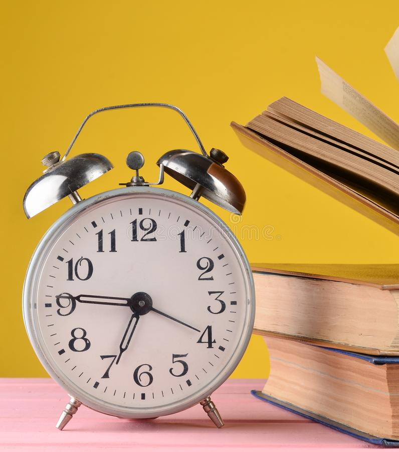 Retro alarm clock and books on a pink table on a yellow wall background. Retro alarm clock and books on a pink table on a yellow wall background stock images