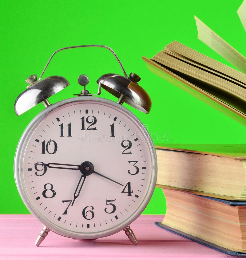 Retro alarm clock and books on a pink table on a yellow wall background. Retro alarm clock and books on a pink table on a yellow wall background stock photography