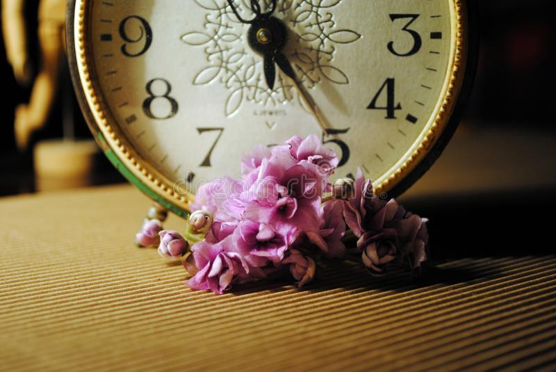 Retro alarm clock, a bunch of violets and a wooden marionette royalty free stock image