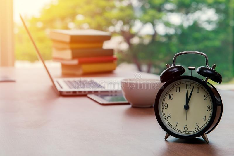Retro alarm clock with cup of cappuccino on table in office, Coffee Break lunch time stock image