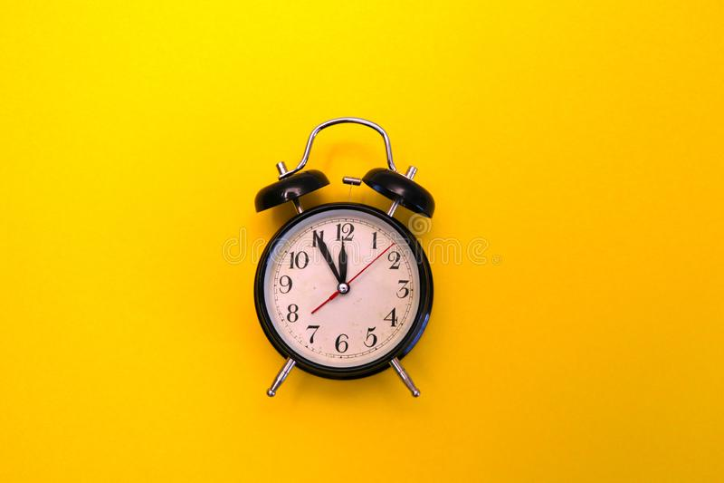 Retro alarm clock isolated on yellow background royalty free stock image