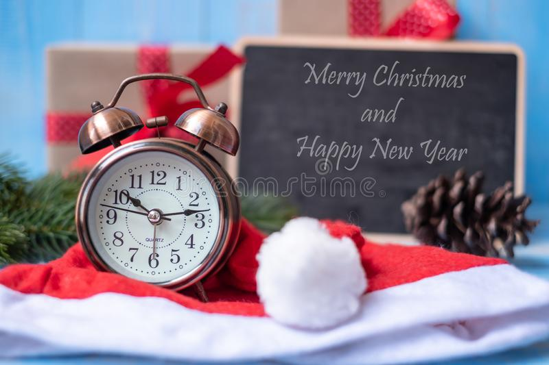 Retro alarm clock with Merry Christmas gift box or Present and Santa Claus hat on blue wooden background royalty free stock photo