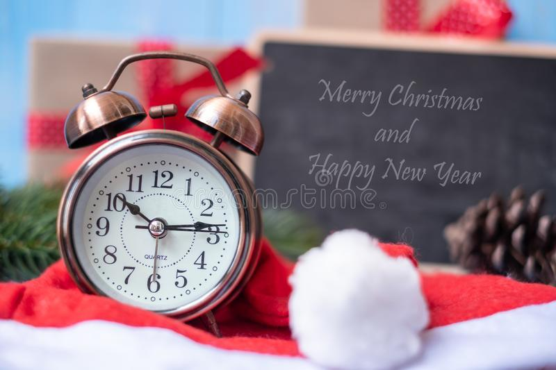Retro alarm clock with Merry Christmas gift box or Present and Santa Claus hat on blue wooden background royalty free stock image