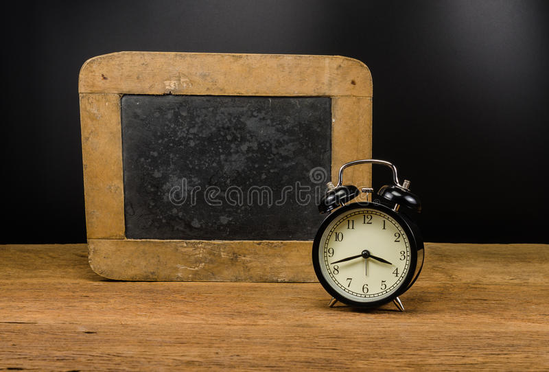 Retro alarm clock and old slate. Retro alarm clock with dirty chalkboard on wooden table,education concept stock images