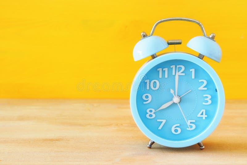 Retro alarm clock over yellow background stock images