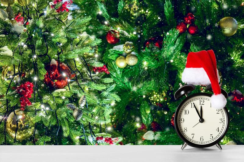 Retro alarm clock with Santa Claus hat against amazing Christmas tree background with Christmas toys and lights.  stock image