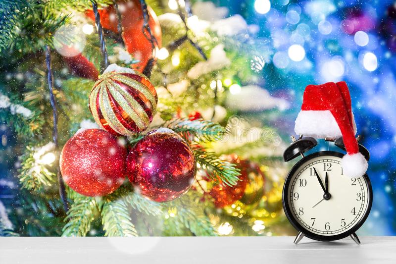 Retro alarm clock with Santa Claus hat against amazing Christmas tree background with Christmas toys, lights and snow.  stock photo
