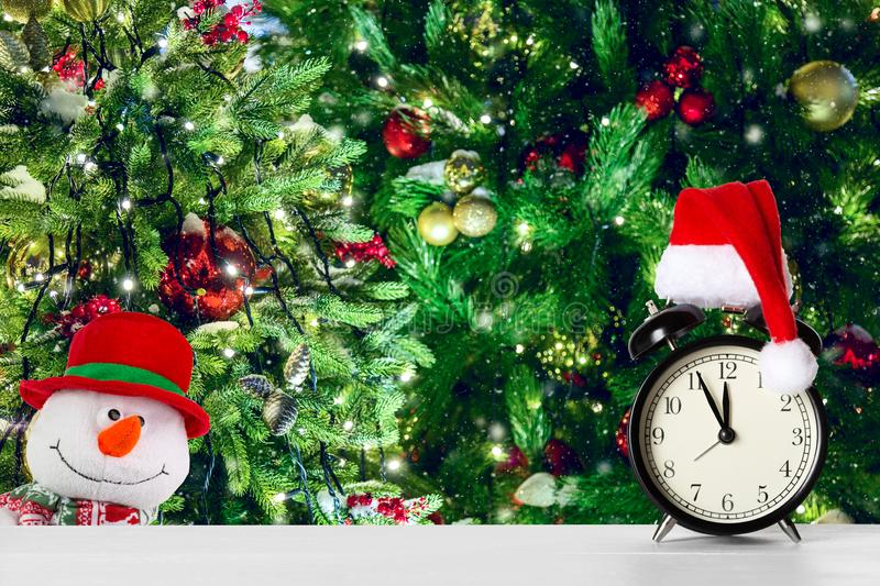 Retro alarm clock with Santa Claus hat and snowman against amazing Christmas tree background with Christmas toys and lights.  stock photography