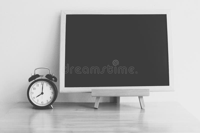 Retro alarm clock setting at 8 o`clock and black board on wood t royalty free stock image