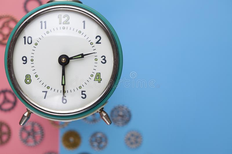 Retro alarm clock and small parts of watch on colored background. Retro alarm clock and small parts of watch on two colored background royalty free stock images