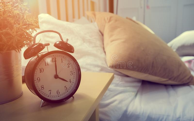 Retro alarm clock standing on a bedside table in a bedroom with royalty free stock photos