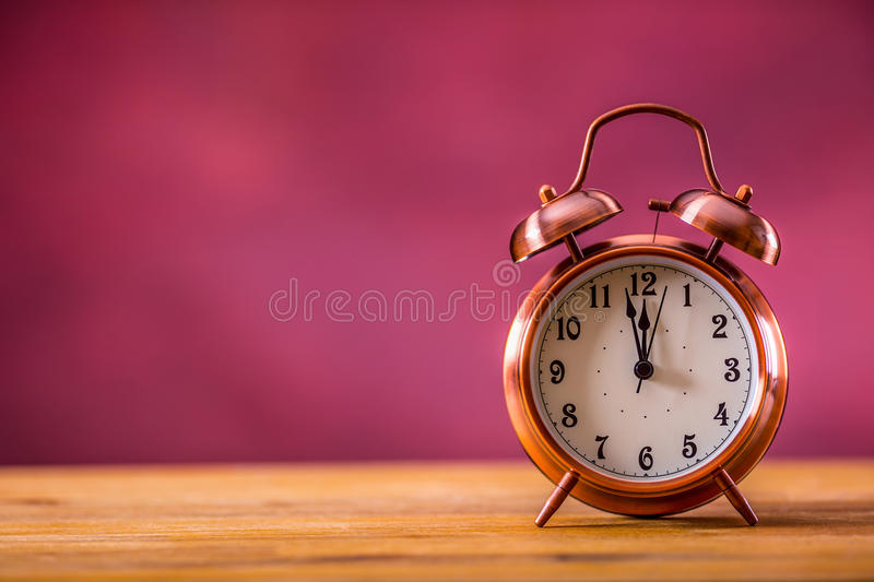 Retro alarm clock with two minutes to midnight. Filtered photo in vibrant colors 50s to 60s. Pink background royalty free stock image