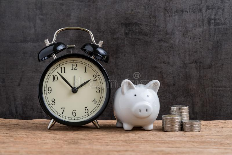 Retro alarm clock with white piggy bank and stack of coins on wooden table and black background as long term savining money or re stock photography