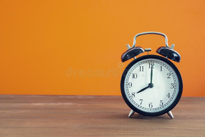 Retro alarm clock on wooden table with orange color background. Vintage style stock image
