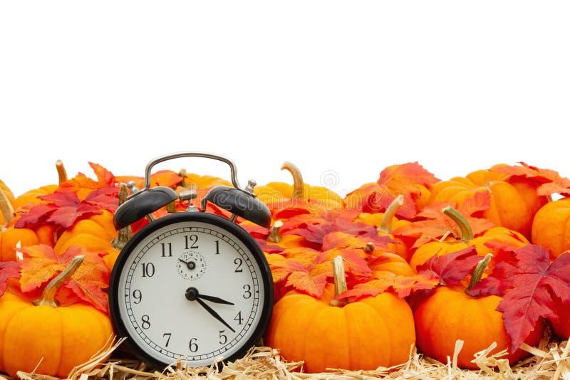 Retro alarm klocka med orangefärgade pumpor med falllöv på halmhö isolerat över vitt royaltyfri foto