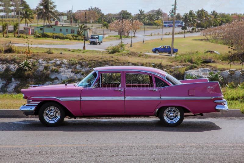 Retro amerikansk rosa bil för klassisk tappning av 1959 från sidoproection som framme sättas av ett bylandskap royaltyfri fotografi