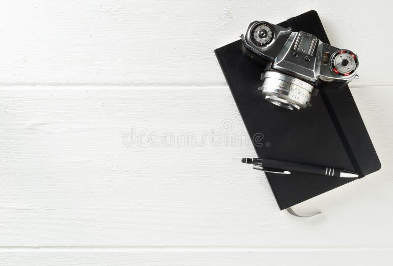 Retro analoge Filmkamera mit Notebook und Stift auf weißem Holztischhintergrund mit Kopierraum - Fotografie, Journalismus, Bloggi lizenzfreie stockfotografie