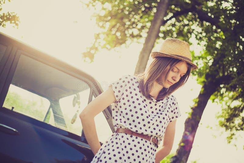 Retro anseende för ung kvinna för stil bredvid bilen royaltyfri fotografi