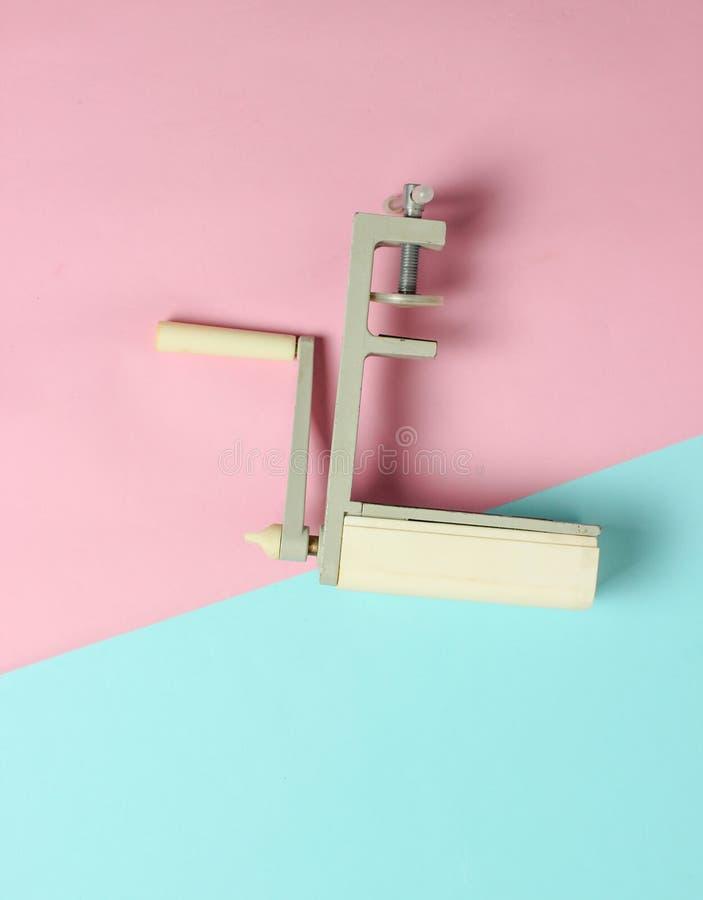Retro apparat för manuell bitande pasta på en pastellfärgad bakgrund Top beskådar minimalism royaltyfri fotografi