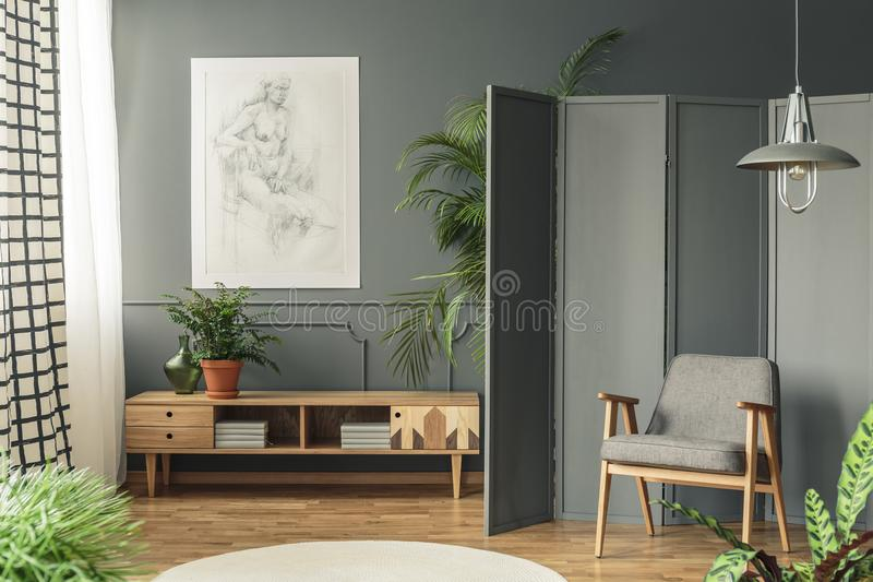 Retro armchair against a gray screen next to a drawing hanging o. N a dark wall with molding above wooden cupboard in living room interior royalty free stock photography