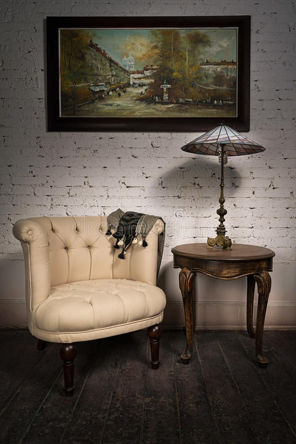 Retro armchair, table lamp on antique table and hanged painting stock photo