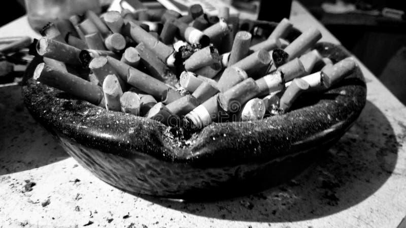 Retro- Aschenbecher voll von Zigarettenkippen stockbilder