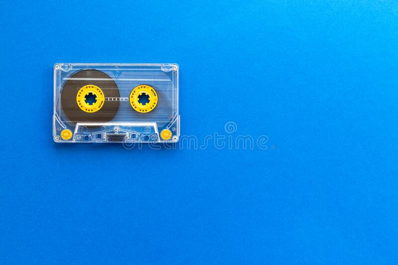 Retro audio tape cassette from 80s and 90s isolated on blue background. Old technology concept. Flat lay, top view with copy space.  royalty free stock photos