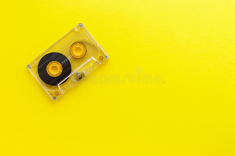 Retro audio tape cassette from 80s and 90s isolated on yellow background. Old technology concept. Flat lay, top view with copy spa. Ce stock image