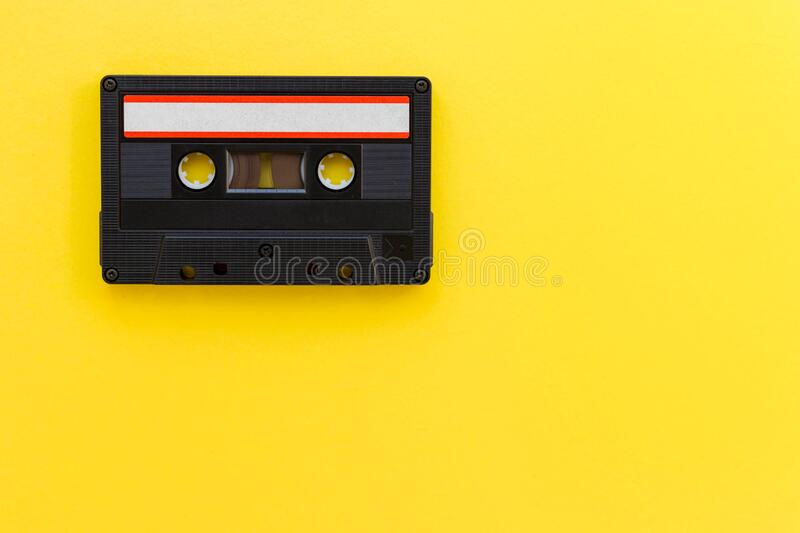 Retro audio tape cassette from 80s and 90s isolated on yellow background. Old technology concept. Flat lay, top view. With copy space stock photography