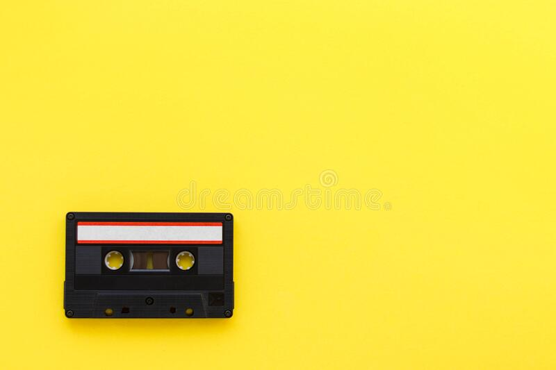 Retro audio tape cassette from 80s and 90s isolated on yellow background. Old technology concept. Flat lay, top view. With copy space stock image
