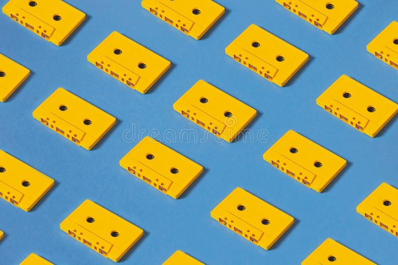 Yellow Audio Cassette Tapes On Blue Background. Creative Concept Of Retro Technology royalty free stock photography