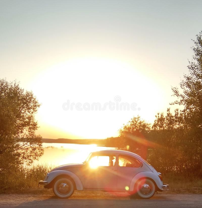 retro auto door het meer bij zonsondergang stock afbeelding