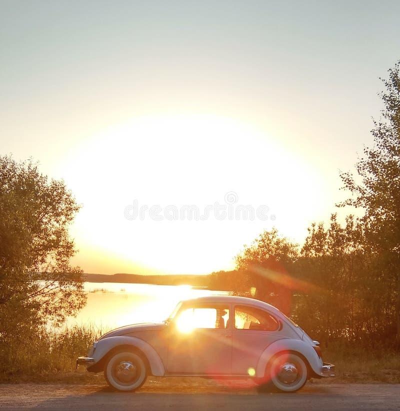 Retro- Auto durch den See bei Sonnenuntergang stockbild