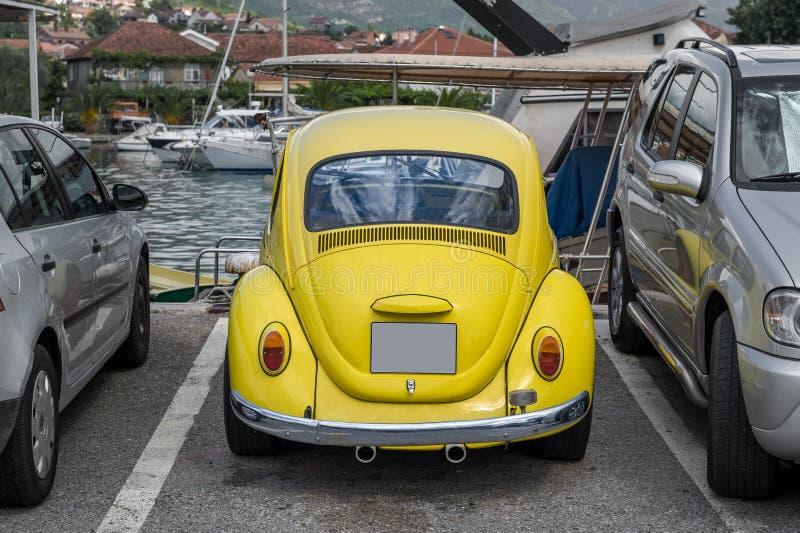 Retro automobile gialla al porticciolo dell'yacht immagini stock libere da diritti