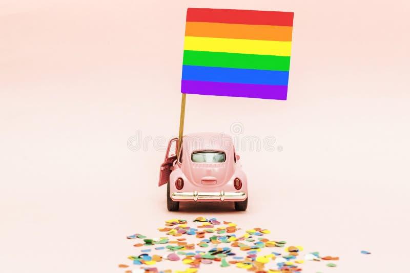 Retro automobile rosa del giocattolo che consegna la bandiera gay dell'arcobaleno luminoso su backgraund rosa molle che lascia un immagini stock