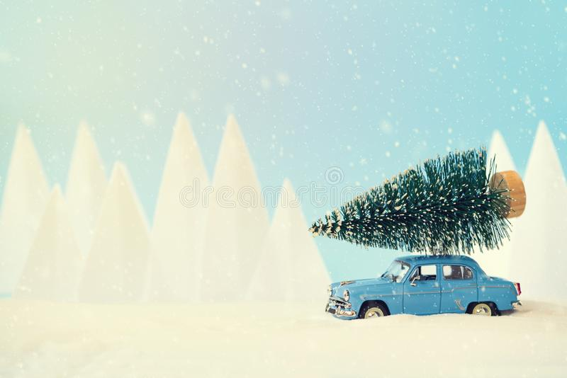 Retro- Autospielzeug tragender Weihnachtstannenbaum in der schneebedeckten Landschaft Weihnachts- oder Feierkonzept des neuen Jah lizenzfreie stockbilder