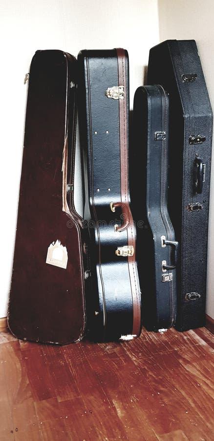 Retro będący ubranym gitary skrzynki * przeciw ścianie zdjęcia stock