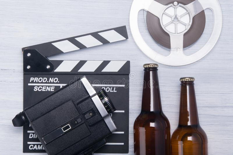 Retro background, with a set of items for viewing and a video camera with a film on the double for filming, with two beer bottles royalty free stock photography