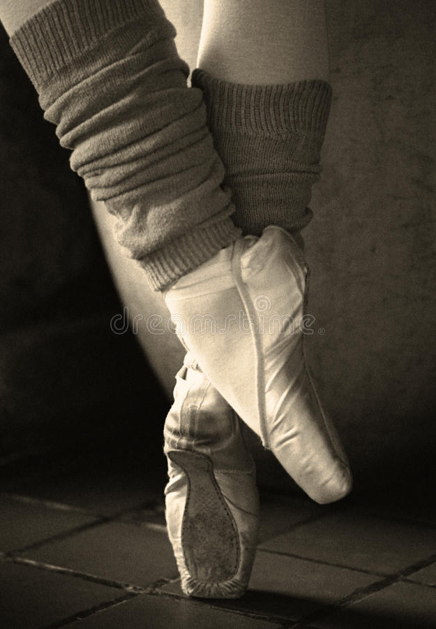 Retro Ballerina Feet. Close-up of ballerina feet & leg warmers. Vintage picture with noise added stock photo
