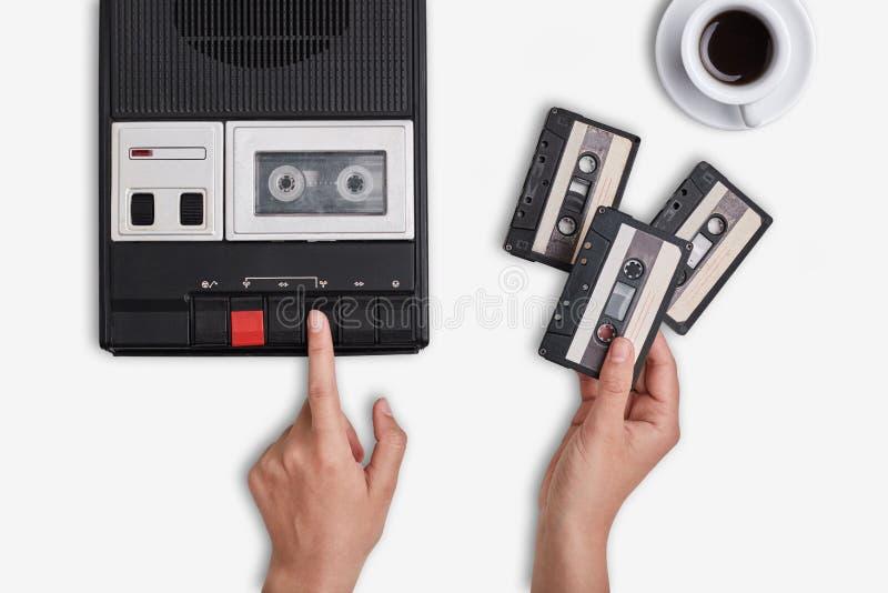Retro bandspelare, kassetter och kopp av varmt kaffeanseende på vit yttersida Händer som kopplar på att ändra för kassettbandspel royaltyfri bild