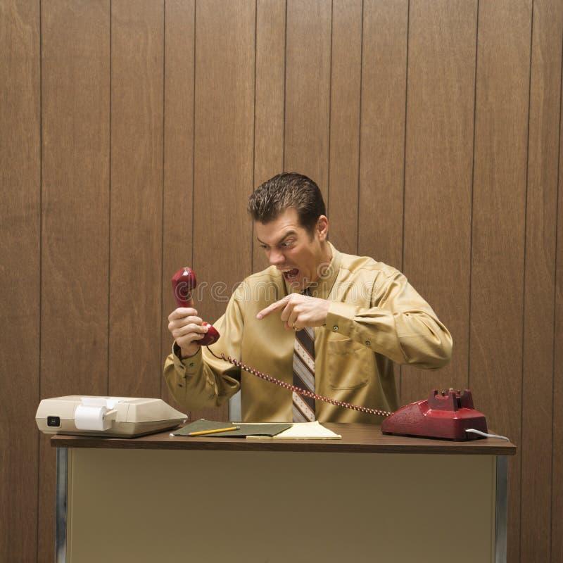 Retro bedrijfsscène van de boze mens bij bureau. royalty-vrije stock foto's