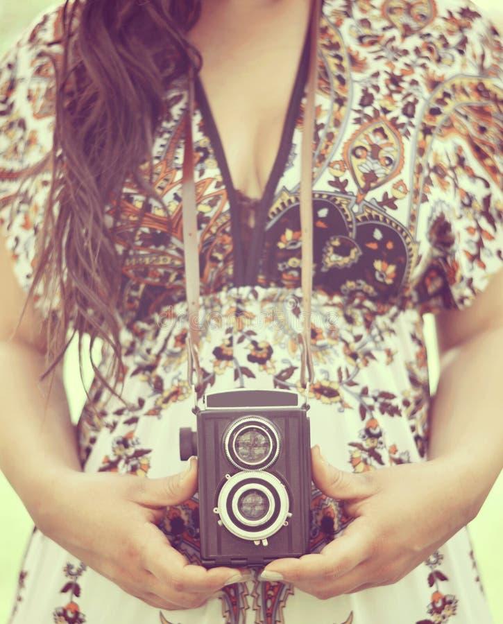 Retro beeld die van vrouwenhanden uitstekende camera in openlucht houden stock afbeelding